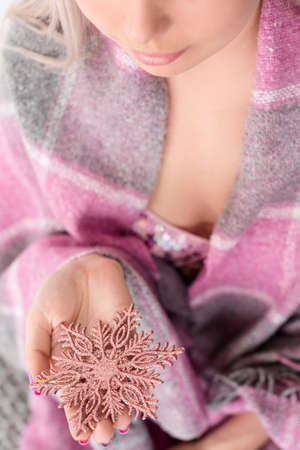 magic of christmas and winter coziness and home comfort. woman holding a rose gold shiny snowflake in hands covered in warm blanket. happy new year holidays and festivities.