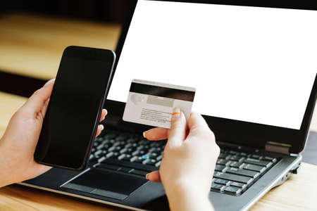 two factor authentication. identity verification. security code to access financial data online. woman hands holding bank card and mobile phone. white blank laptop screen for e-commerce.