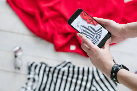 still life mobile photography. hobby and creative lifestyle concept. woman taking photos of clothing on smartphone. Stock Photo