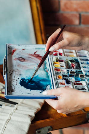 art painting hobby. creative lifestyle. artist mixing watercolors preparing to draw picture. ink dyes colorful palette. talent inspiration creation and self expression concept 스톡 콘텐츠