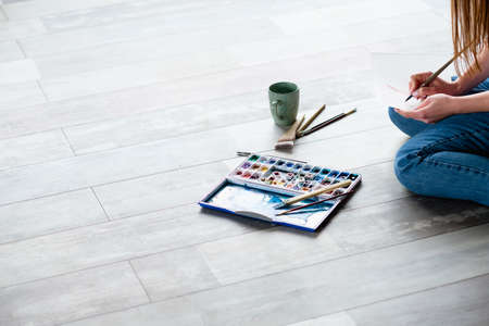 creative leisure. painting hobby. artful personality. talented artist drawing sitting on the floor.