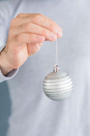 christmas balls. elegant festive decor and new year holiday ornaments concept. man holding silver glittery baubles in hands.