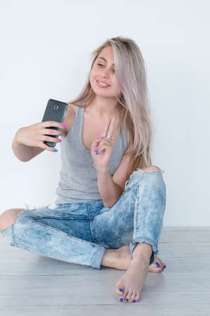 young beautiful girl taking a selfie using smart phone. carefree idle leisure and social network posting concept.