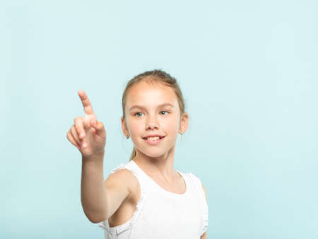 smiling girl reaching and wanting to press invisible button in front of her. interface or virtual screen concept. free space for advertisement or text. portrait child on blue background.