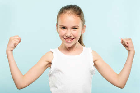 emotion expression. victory yes. very happy joyful thrilled to bits child with beaming smile and hands in the air. young cute girl portrait on blue background.