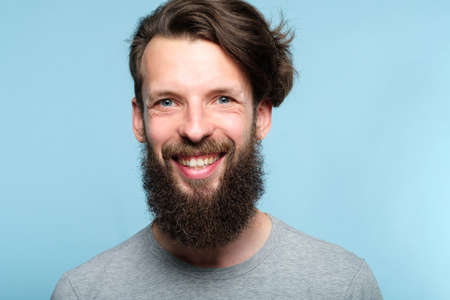 emotion expression. happy joyful smiling man. young handsome bearded hipster guy portrait on blue background.
