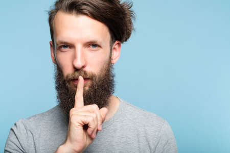 shh silence and quiet concept. man showing finger on lips gesture. portrait of a bearded hipster guy on blue background.