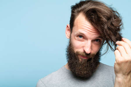 male hair styling problems because of modern long hairdo fashion. haircare products concept. bearded hipster man portrait on blue background looking at his locks.