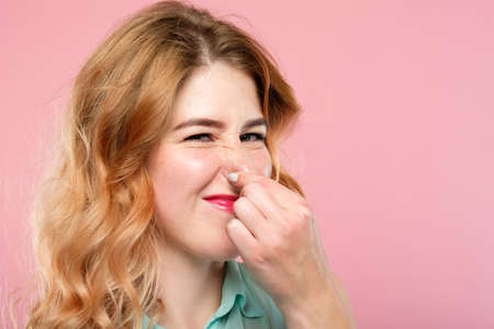 bad rancid smell or terrible odor concept. woman holding her nose and grimacing. emotion expression and reaction concept. young beautiful blond girl portrait on pink background. Stock Photo