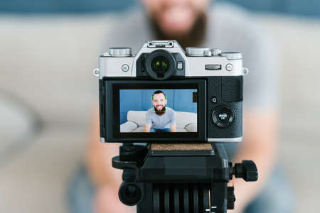 social media influencer creating content. man shooting video of himself using camera on tripod. modern technology and equipment concept. Stock Photo