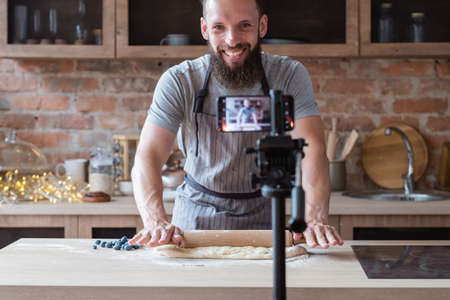 food blogger streaming live. bearded hipster man communicating with subscribers through phone camera. chef rolling out dough with a pin. Stock Photo