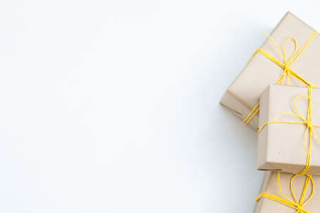 christmas presents in gift boxes wrapped in craft paper and tied with a yellow twine. three packages on white background with free space