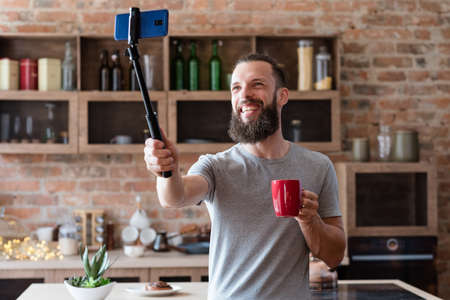 vlogger streaming live using mobile phone camera on selfie stick. bearded hipster man communicating with subscribers standing at home kitchen. Stock Photo