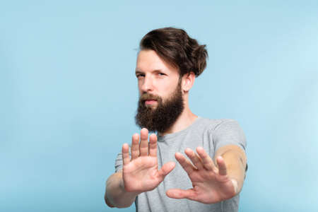 no thanks. rejection refusal and denial. young casual hipster man putting hands forward as if pushing smth away. portrait of a bearded guy on blue background. 写真素材