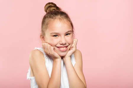 cute smiling pretty girl. little carefree happy child portrait on pink background. emotion and facial expression concept.