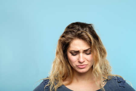 crying tearful stressed woman. portrait of a sad gloomy depressed sorrowful melancholy young girl on blue background. Stock Photo