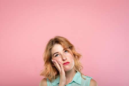 Gesichtsausdruck. schlechte Laune und Emotionen. gelangweilte unbeeindruckte desinteressierte Frau, die aufschaut. junges schönes blondes Mädchenporträt auf rosa Hintergrund.