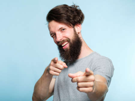 you rock man. success and approval concept. confident positive guy winking at viewer and pointing index fingers. casual hipster guy portrait on blue background. Stock Photo