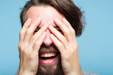 emotion expression. happy joyful smiling man covering face with hands. young handsome bearded hipster guy portrait on blue background.