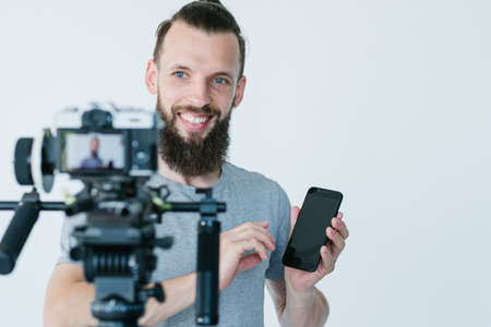 social media influencer at work. blogger shooting a commercial or independent review. man holding a mobile phone in front of a camera. hobby turned into lucrative business. Stock Photo