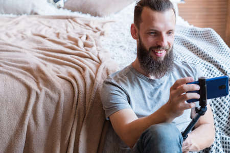 bearded hipster man taking a selfie using phone camera on a stick. idle leisure and relaxed carefree lifestyle. guy sitting at home near the bed. modern social trends concept. 版權商用圖片