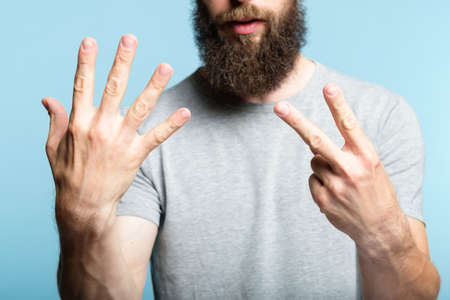 bearded man showing number seven with his hand. cropped shot of a male torso on blue background. casual hipster in grey t-shirt counting gesture. 版權商用圖片