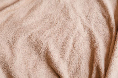 crumpled pink beige fleece blanket. comfy and warm cover. plush fabric texture background. copyspace concept.