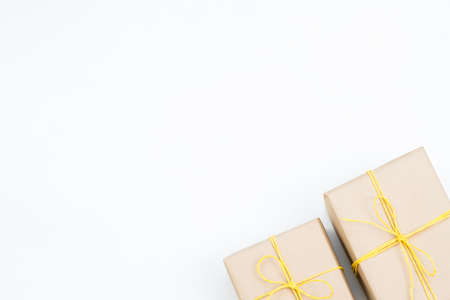 holiday presents in gift boxes wrapped in craft paper and tied with a yellow twine. two packages on white background with copyspace.