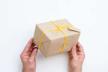 handcrafted present. heartfelt congratulation and reward for a special person. hands holding gift wrapped in paper and tied with yellow twine. festive package on white background.