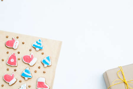 festive season background. handmade gingerbread christmas cookies and packaged gift on white backdrop with copyspace. 스톡 콘텐츠