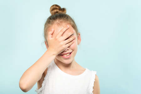 facepalm embarrassment and shame emotion. ashamed smiling girl covering her face with a hand. young cute child portrait on blue background.