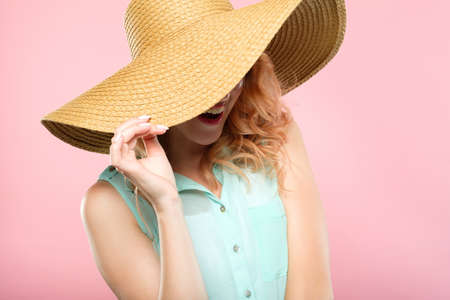 summer vacation and touring trips concept. young pretty woman in a big sunhat ready to go to the beach. cute stylish joyful girl portrait on pink background. Stock Photo