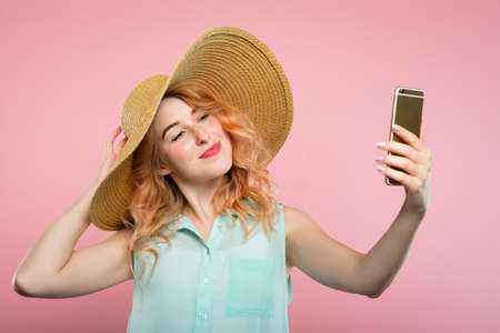 selfie and self adoration. young stylish woman in a big sunhat taking a photo of herself using mobile phone. modern lifestyle and trends. Stock Photo