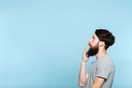 man looking sideways and is shocked or impressed by smth on the left. free space for advertisement or text. portrait of a bearded guy on blue background.