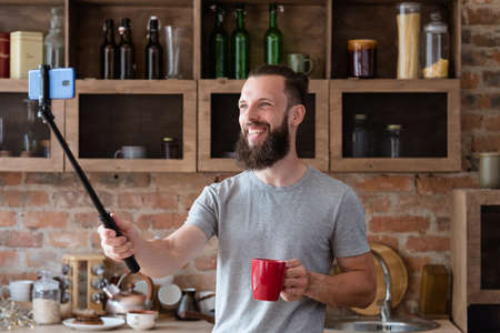 blogger streaming live video using mobile phone camera and selfie stick. bearded hipster man communicating with subscribers from his kitchen. Stock Photo