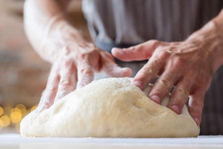 cursos de panadero. preparación de alimentos y concepto de clase de formación culinaria. manos de hombre listas para amasar la masa. Foto de archivo