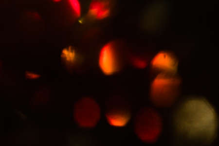 abstract lens flare on black background. red defocused bokeh lights. blurred christmas wallpaper decor. festive glowing circles design.