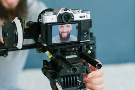 modern technology for photo and video shooting. camera on tripod. blogger equipment and tools. image of a man on screen.