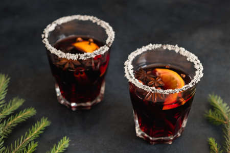 festive cozy christmassy atmosphere. holiday hot drink to warm up. two glasses of spicy mulled wine on black background. Archivio Fotografico - 107792526