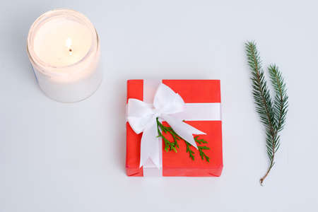 christmas present giving tradition concept. gift in a red wrapping paper with a ribbon bow on white background. burning candle and fir tree twig decoration.