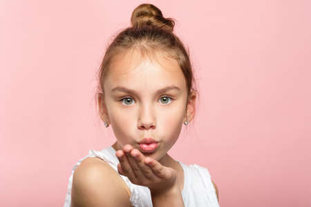 cute little girl blowing a kiss. pretty young child sending love. romance and warm feelings concept. portrait on pink background. Фото со стока