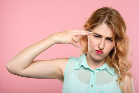kill me please. bullet to the head. girl pointing a finger gun to her temple. emotional breakdown and stress concept. portrait of a beautiful girl on pink background. Foto de archivo