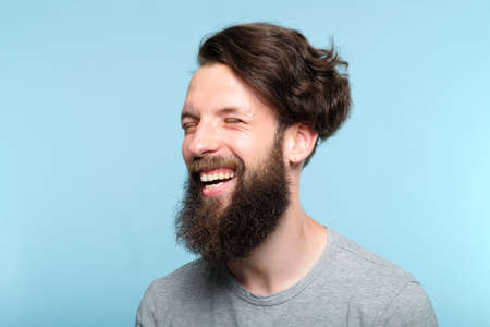 emotional facial expression. happy joyful smiling man. young handsome bearded hipster guy portrait on blue background.