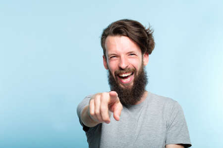 young bearded hipster man mocking and laughing at viewer pointing finger. mockery sneer jeer concept. portrait of a grinning guy on blue background.