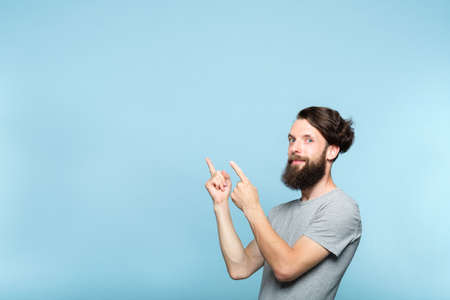 young man pointing left with both hands to a virtual object or text. copy space for advertisement or product placement. portrait of a bearded hipster guy on blue background.