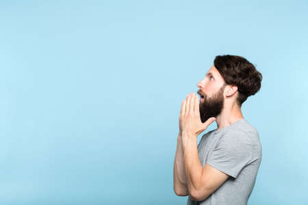 man looking sideways and is amazed or impressed by smth on the left. free space for advertisement or text. portrait of a bearded guy on blue background. 写真素材