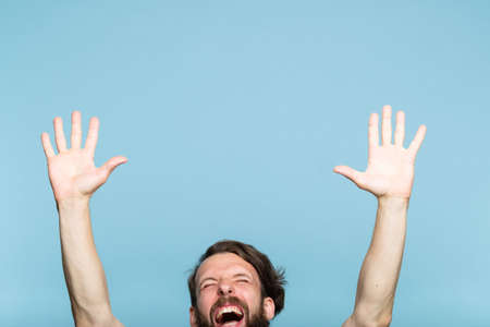 happiness enjoyment and laugh. excited man with hands in the air. portrait of a young bearded guy on blue background. emotion facial expression. feelings and people reaction. Reklamní fotografie