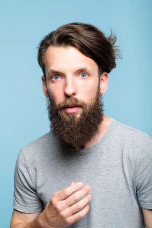 omg unbelievable shock. speechless dumbstruck man. portrait of a young bearded guy on blue background. emotion facial expression and reaction concept.