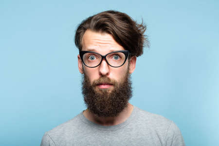 worried nervous alarmed bearded hipster guy wearing cat eye glasses. stylish modern fashionist. portrait of a geeky quirky eccentric man on blue background. 版權商用圖片