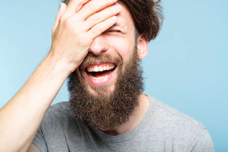 facepalm. happy smiling joyful man covering his face. shame and fun concept. portrait of a young bearded guy on blue background. emotion facial expression.